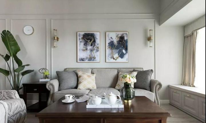 客厅布艺沙发搭配简约线条背景墙,点缀金色元素装饰画与对称壁灯,并靠图片